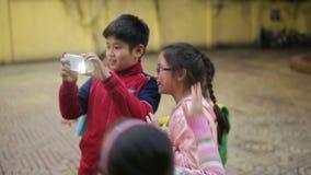 Ханой, Вьетнам - 12-ое марта 2015: Дети используя мобильный телефон видеоматериал