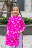 Ханой, Вьетнам - 7-ое февраля 2015: Маленькая девочка с въетнамским традиционным длинным платьем Ao Dai играя на въетнамском лунн стоковое изображение