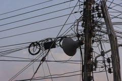 Хаотический переплетаясь беспорядок линий электропередач электричества на поляке стоковые изображения