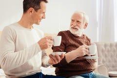 Харизматический пенсионер слушая к его внуку стоковая фотография rf