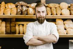 Харизматический хлебопек стоит на предпосылке полок со свежим хлебом  стоковое фото