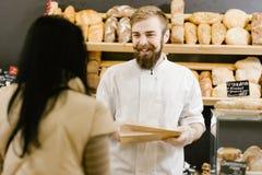Харизматический хлебопек с бородой и усиком дает бумажный мешок хлеба клиенту в пекарне стоковая фотография
