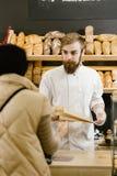 Харизматический хлебопек с бородой и усиком дает бумажный мешок хлеба клиенту в пекарне стоковое фото rf