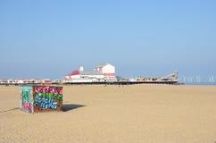 Хата найма Deckchair на пляже на Great Yarmouth с пристанью удовольствия в хате предпосылки и graffitti на фронте стоковое фото rf