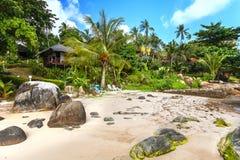 Хаты гостиницы в растительности, среди пальм на песчаном пляже Стоковое Фото