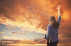Хваления женщины во время захода солнца стоковое фото rf