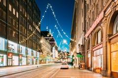 Хельсинки, Финляндия Взгляд ночи улицы Aleksanterinkatu с железной дорогой Стоковое Фото