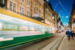 Хельсинки, Финляндия Трамвай уходит в нерезкости движения от стопа на улице Aleksanterinkatu в районе Kluuvi в ноче вечера Стоковая Фотография