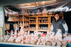 Хельсинки, Финляндия Человек продавая подарки сувениров рождества в форме кондитерскаи от пряника на европейской зиме Стоковые Изображения