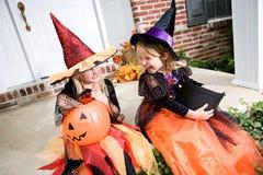 Хеллоуин: Девушки сидят на парадном крыльце с конфетой фокуса или обслуживания Стоковая Фотография