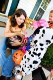 Хеллоуин: Родитель вручая вне конфету на хеллоуине Стоковое Фото