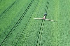 Химикаты сельско-хозяйственной техники вида с воздуха распыляя на большом зеленом цвете Стоковая Фотография