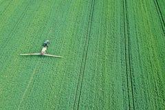 Химикаты сельско-хозяйственной техники вида с воздуха распыляя на большом зеленом цвете Стоковое Изображение