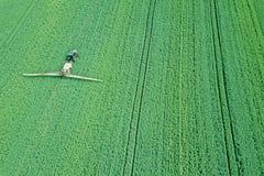Химикаты сельско-хозяйственной техники вида с воздуха распыляя на большом зеленом цвете стоковые изображения