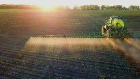 Химикаты трактора распыляя в поле на заходе солнца акции видеоматериалы
