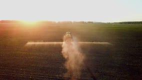 Химикаты трактора распыляя в поле на заходе солнца видеоматериал