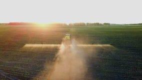 Химикаты трактора распыляя в поле на заходе солнца сток-видео