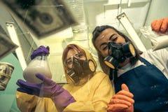 2 химика молодых женщин работая на научной лаборатории с лекарствами Стоковая Фотография