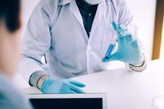 Химик описывает вещество в beaker в лаборатории стоковое фото