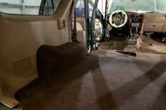 Химическая чистка покрытия пола автомобиля коричневого, места извлекла, приборная панель демонтировала, электрические кабели види стоковое фото rf