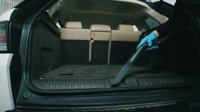 Химическая чистка хобота, человека очищает интерьер автомобиля с пылесосом акции видеоматериалы