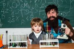 Химия класс науки Ребенок школьного возраста Сын папы сконцентрирован на проблеме Планы урока - средняя школа стоковые изображения rf