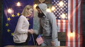 Хипстеры женщина и человек тряся руки над американцем и флагами ЕС Рукопожатие над американцем и флагами ЕС Сотрудничество сток-видео
