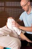 Хиропрактор регулируя мышцы ноги с тренировкой Стоковые Изображения RF
