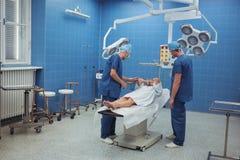 Хирурги взаимодействуя с пациентом во время деятельности стоковое изображение