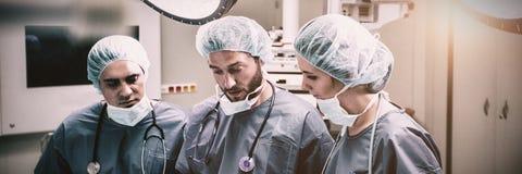 Хирурги обсуждая над цифровой таблеткой в комнате деятельности стоковые фотографии rf