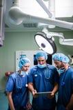 Хирурги обсуждая над цифровой таблеткой в комнате деятельности Стоковая Фотография RF