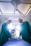 Хирурги обсуждая над цифровой таблеткой в комнате деятельности Стоковые Изображения