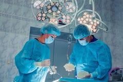 Хирурги объединяются в команду работа с контролем пациента в хирургическом ope стоковое изображение rf