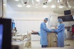 Хирурги рассматривая пациента в театре деятельности стоковое фото rf