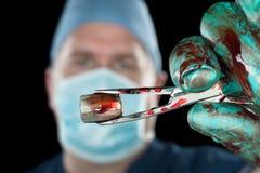 Хирург держа пулю Стоковое Фото