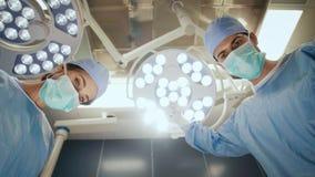 Хирург устанавливая хирургический свет во время деятельности сток-видео