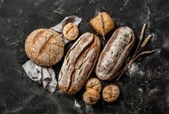 Хлебопекарня - деревенские покрытые коркой ломти хлеба и плюшки на черноте Стоковое Изображение RF