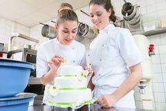 2 хлебопека печенья украшая большой торт стоковые фотографии rf