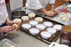 Хлебопеки делая плюшки для печь Стоковое Фото