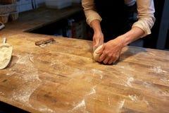Хлебопек делая тесто хлеба на кухне хлебопекарни Стоковое Изображение RF