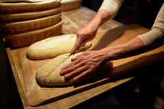 Хлебопек делая хлеб и режа тесто на хлебопекарне Стоковые Изображения