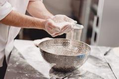 Хлебопек добавляет муку к тесту в шаре утюга на таблице в пекарне стоковая фотография rf