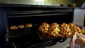 Хлебопек извлекая поднос испеченных печениь от печи сток-видео