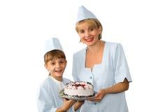 Хлебопек и девушка с замороженным тортом Стоковая Фотография RF