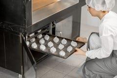 Хлебопек кладя плюшки в печь Стоковая Фотография