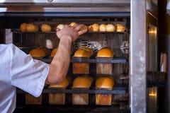 Хлебопек печет хлеб стоковое изображение rf