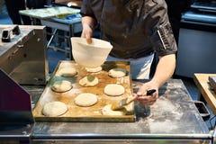Хлебопек подготавливает плюшки для печь Стоковое фото RF