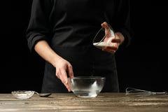 Хлебопек подготавливая тесто дрожжей, на темной предпосылке Подготовка концепции и теста пекарни стоковое фото rf
