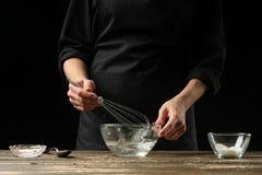 Хлебопек подготавливая тесто дрожжей, на темной предпосылке Подготовка концепции и теста пекарни стоковые фото