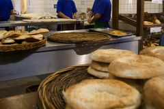 Хлебопек просеивая муку через сетку в магазине пекарни стоковое изображение rf